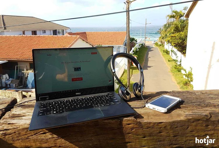 a laptop on a balcony a block from the ocean