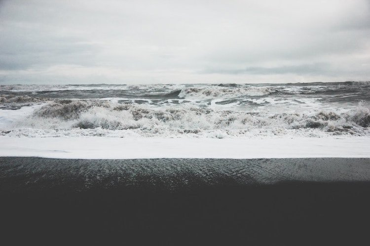 waves breaking on a black sand beach on a cloudy day